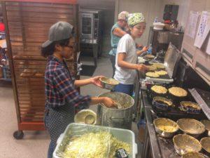 Volunteers cooking pancakes